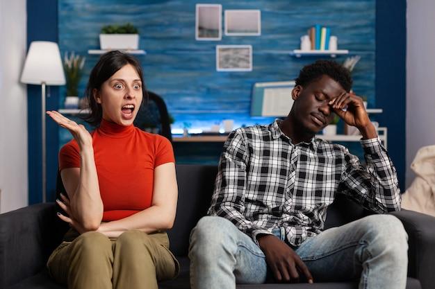 Casal interracial discutindo sentado em casa. parceiros mestiços irritados brigando e tendo disputa de relacionamento. mulher caucasiana zangada a gritar com um homem afro-americano