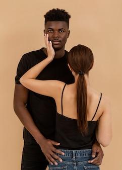 Casal interracial em plano médio posando
