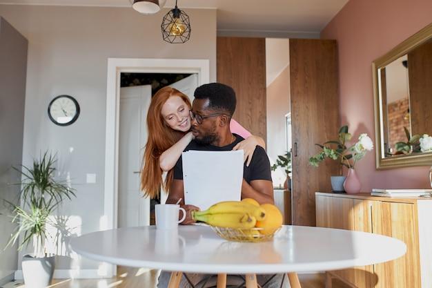 Casal interracial lendo correspondência e verificando a contabilidade na cozinha de casa