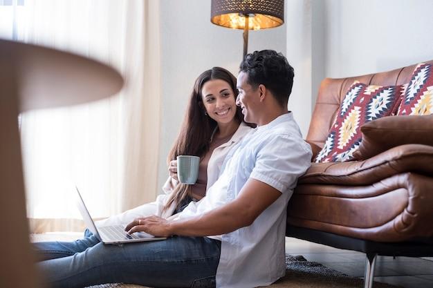 Casal interracial menino e menina usam o laptop em casa, sentados no chão contra o sofá