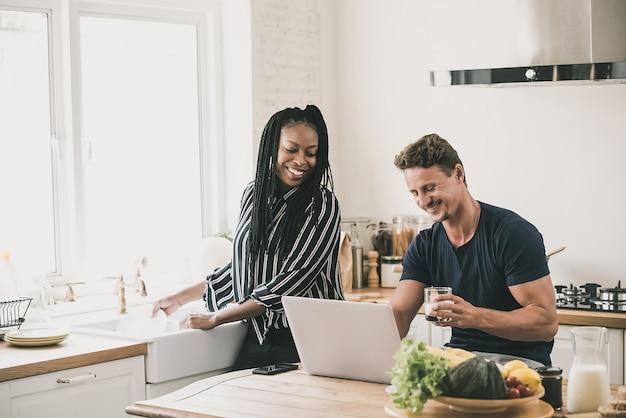 Casal interracial olhando para laptop juntos em casa