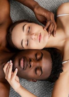 Casal interracial posando com os olhos fechados