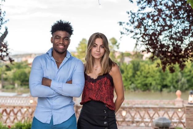 Casal interracial posando juntos. menino negro afro com cabelo encaracolado e uma menina loira caucasiana.