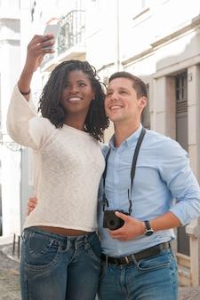 Casal interracial positivo tirando foto de selfie ao ar livre