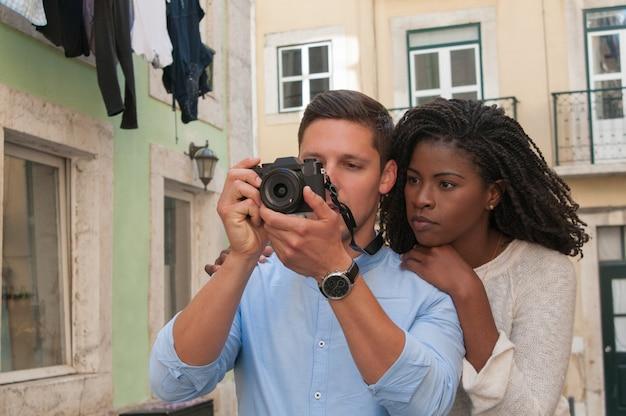 Casal interracial sério tirando fotos na câmera na cidade