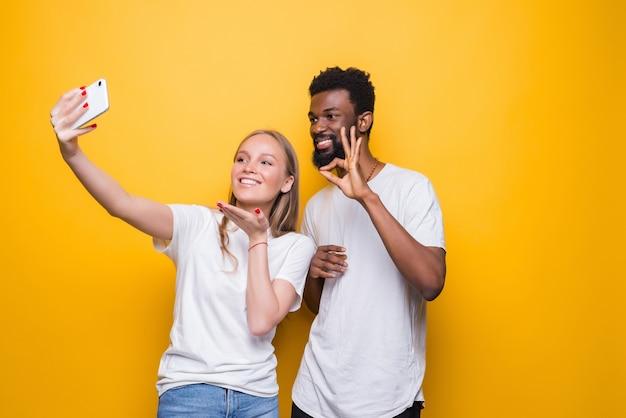 Casal interracional alegre fazendo autorretrato juntos, olhando para a frente e sorrindo, posando sobre a parede amarela