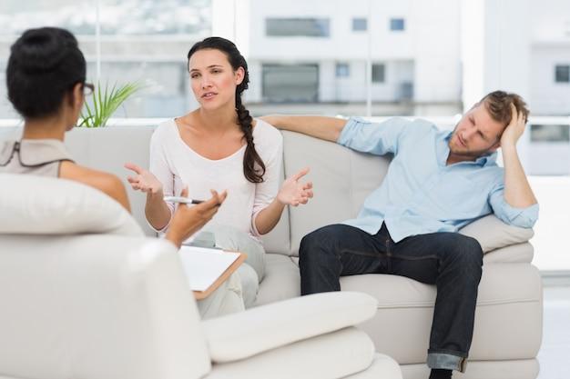 Casal irritado sentado no sofá falando com terapeuta
