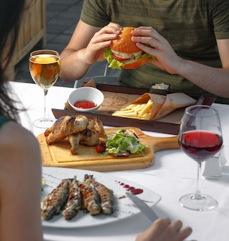 Casal jantando com hambúrguer, peixe e branco, vinho tinto.