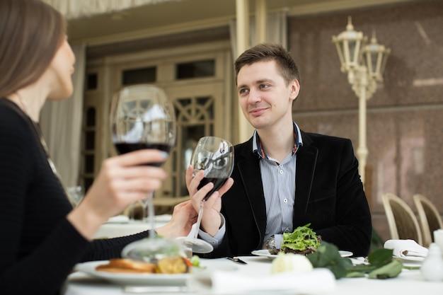 Casal jantando em um restaurante e fazendo um brinde