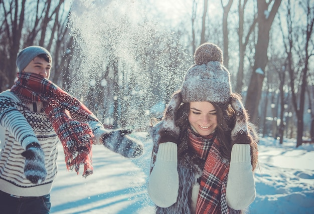 Casal joga neve em winter park. pessoas se divertindo