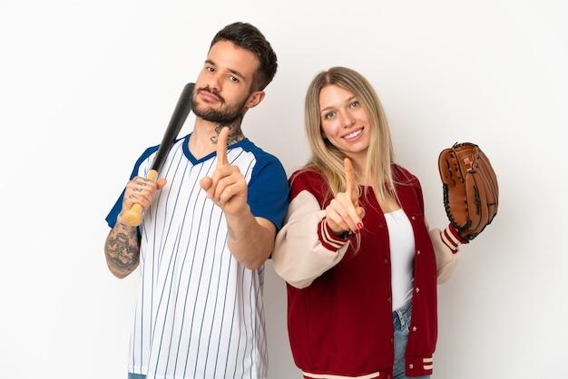 Casal jogando beisebol sobre fundo branco isolado, mostrando e levantando um dedo