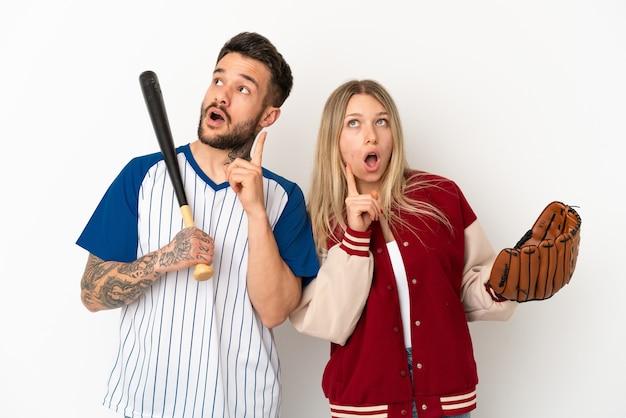 Casal jogando beisebol sobre fundo branco isolado pensando uma ideia apontando o dedo para cima