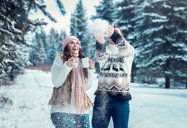 Casal jogando neve na floresta de inverno