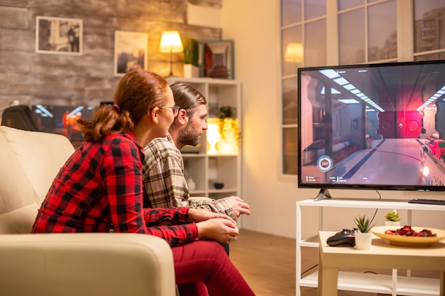 Casal jogando videogame na tv de tela grande na sala de estar tarde da noite.