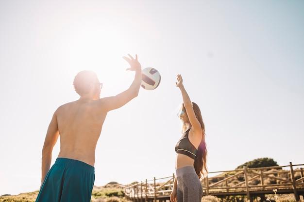 Casal jogando vôlei na praia