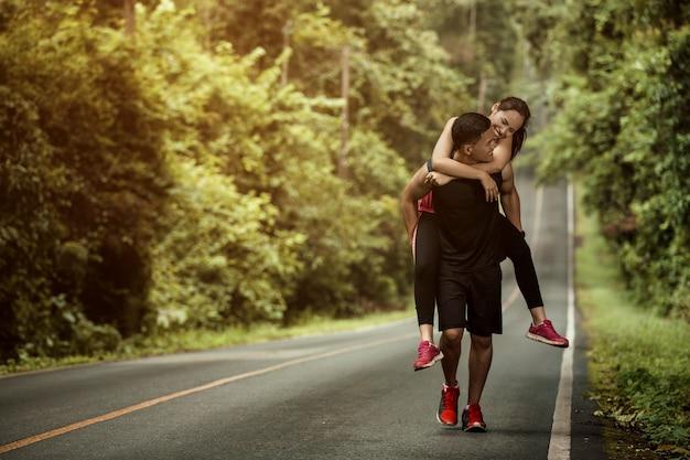 Casal jogging baseado em uma mulher alta para o namorado levá-la para a linha de chegada.