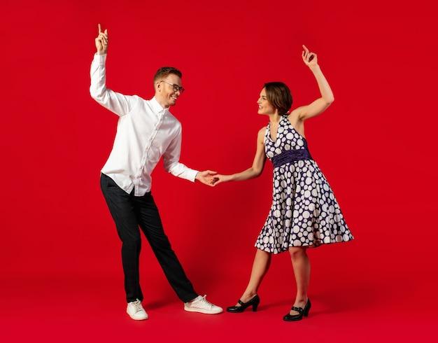 Casal jovem à moda antiga dançando isolado sobre fundo vermelho