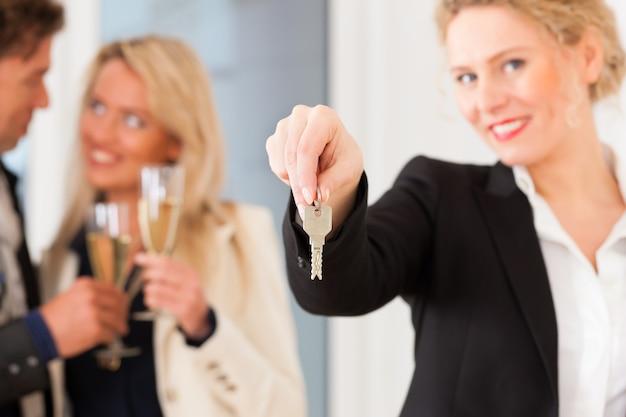 Casal jovem à procura de imóveis com corretor de imóveis feminino