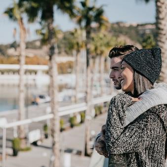 Casal jovem abraçando na frente das palmeiras