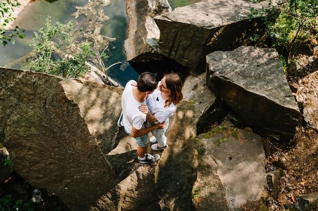 Casal jovem abraçando uma pedra perto do lago olhando um para o outro