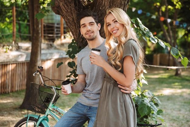 Casal jovem adorável e feliz descansando com um café e olhando para a câmera ao ar livre