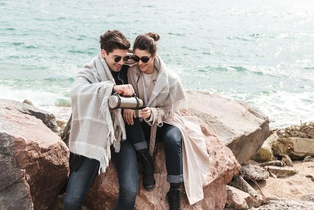 Casal jovem adorável e feliz, vestindo casacos, caminhando na praia, de mãos dadas, bebendo café em uma garrafa térmica