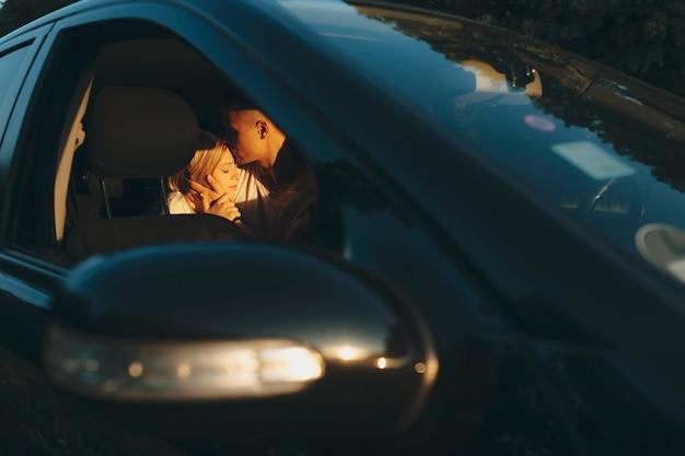 Casal jovem adorável sentado no banco de trás do carro, homem beijando a testa da mulher com os olhos fechados, foto feita pela janela da porta aberta do carro ao pôr do sol