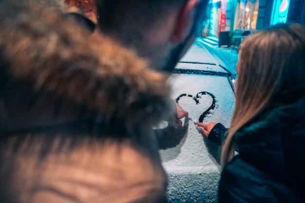 Casal jovem adulto desenha um coração no carro coberto de neve