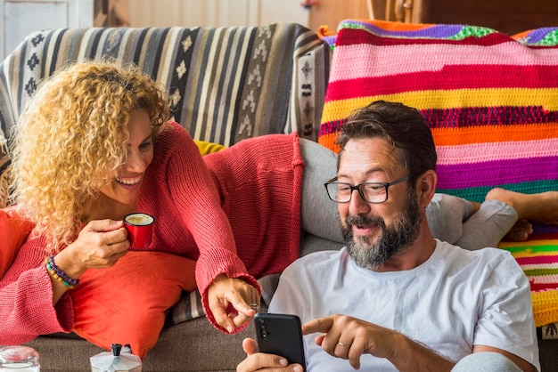Casal jovem adulto feliz se diverte e aproveita o telefone em casa durante a atividade do café da manhã juntos - mulher de meia-idade e homem riem olhando para o celular - pessoas reais com fundo colorido Foto Premium