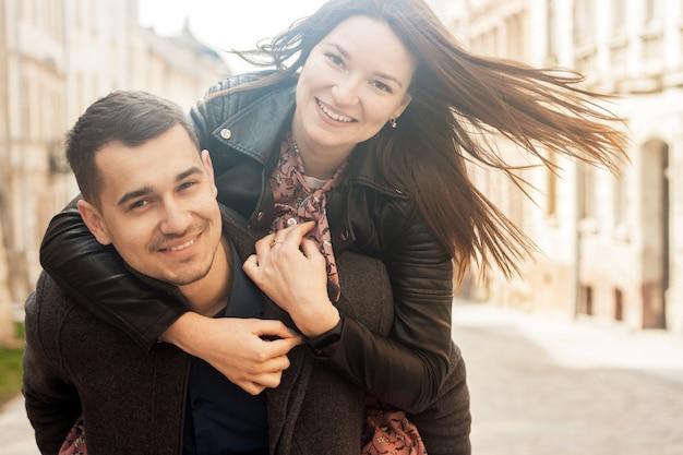Casal jovem alegre abraçando na rua em dia de sol