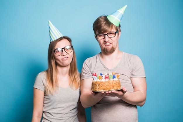 Casal jovem alegre charmoso e linda garota com chapéus de papel faz cara de boba e segura nas mãos um bolo com a inscrição de pé de aniversário em uma parede azul. saudações de conceito e pegadinha