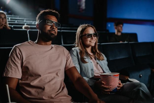 Casal jovem alegre com óculos 3d no cinema, assistindo ao filme.