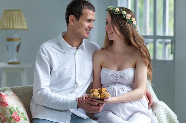 Casal jovem alegre com sapatos de bebê sentado em casa