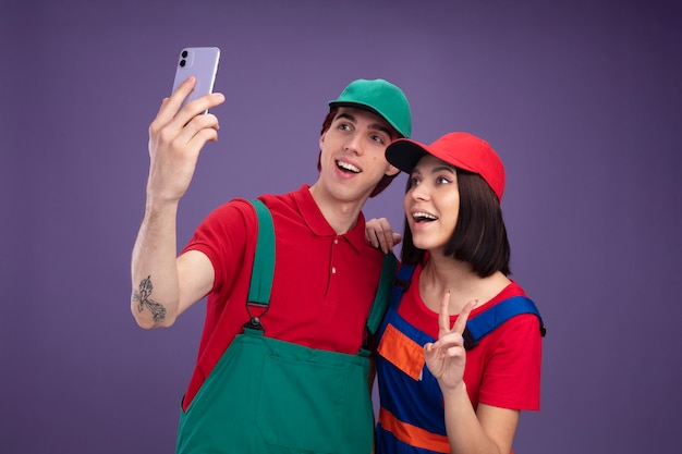 Casal jovem alegre com uniforme de trabalhador da construção civil e boné tomando selfie juntos, garota colocando a mão no ombro do cara, fazendo o sinal da paz