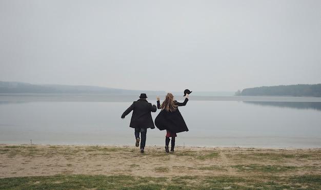 Casal jovem alegre, comemorando seu amor um lago no inverno