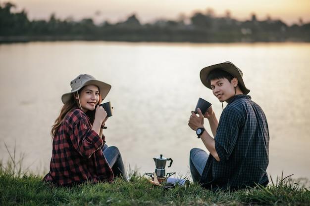 Casal jovem alegre de mochileiros sentado na grama perto do lago no início da manhã fazendo um moedor de café fresco durante o acampamento nas férias de verão