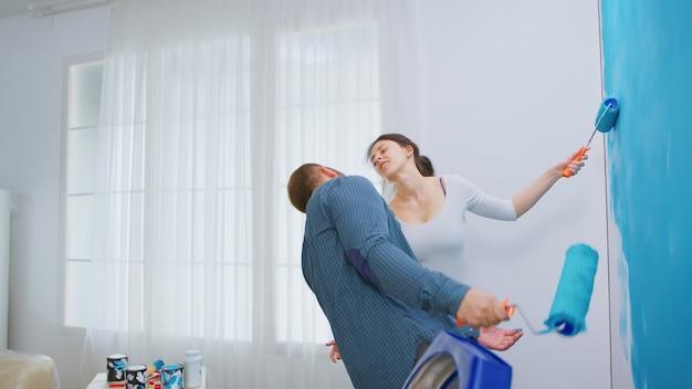 Casal jovem alegre decorando o apartamento e dançando. se divertindo e pintando as paredes. redecoração de apartamento e construção de casa durante a reforma e melhoria. reparação e decoração.