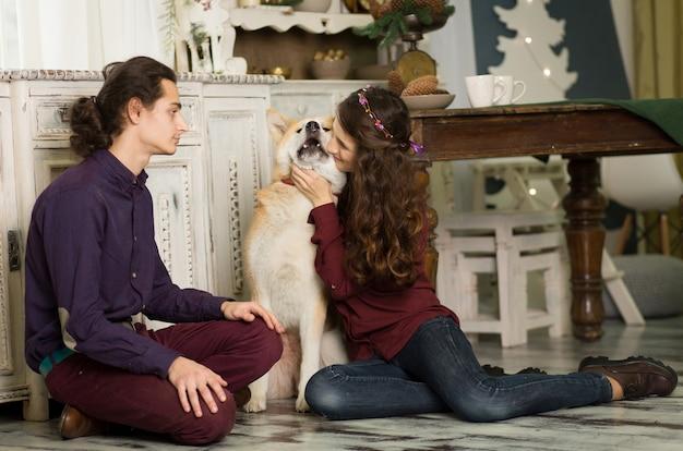 Casal jovem alegre é abraçar e beijar um cachorro da raça akita inu. em decorações de natal em estilo retro