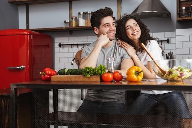 Casal jovem alegre e animado cozinhando uma salada saudável enquanto está sentado na cozinha, olhando para longe