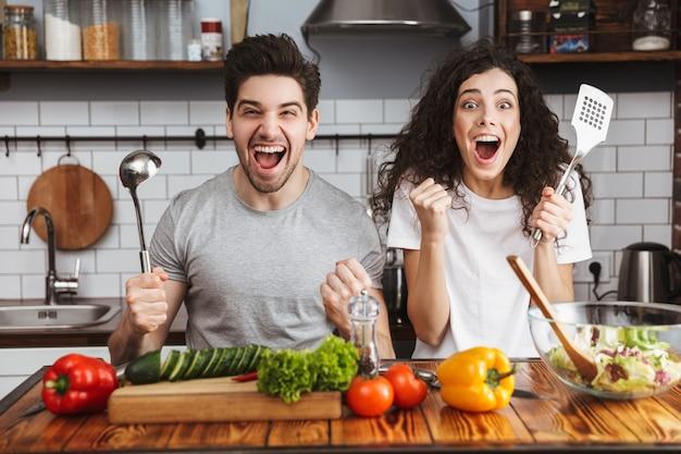 Casal jovem alegre e animado cozinhando uma salada saudável enquanto está sentado na cozinha