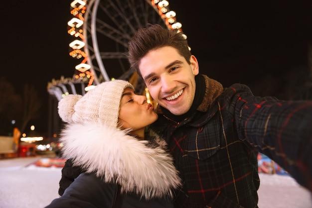 Casal jovem alegre e feliz se divertindo à noite no parque de patinação no gelo, tirando uma selfie, se beijando