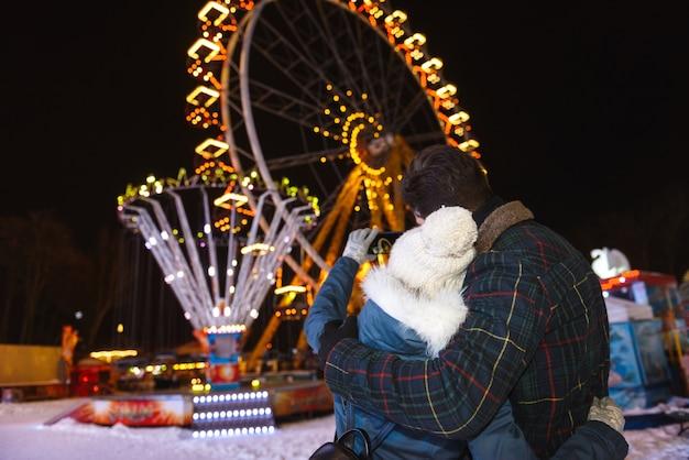 Casal jovem alegre e feliz se divertindo no parque de patinação no gelo à noite, se abraçando