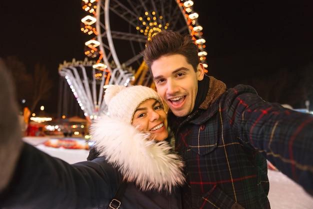 Casal jovem alegre e feliz se divertindo no parque de patinação no gelo à noite, tirando uma selfie