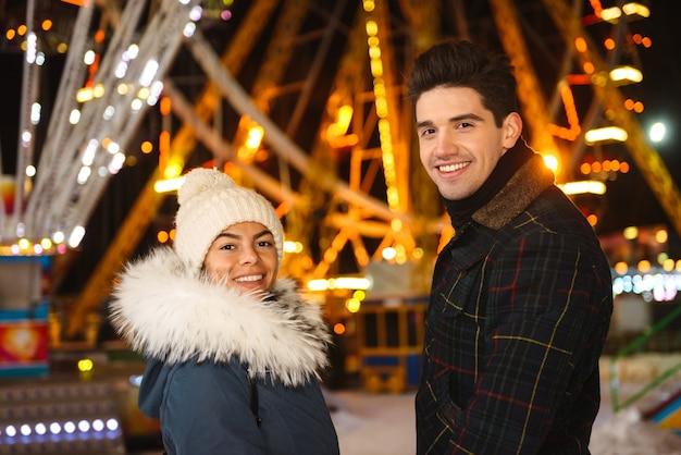 Casal jovem alegre e feliz se divertindo no parque de patinação no gelo à noite
