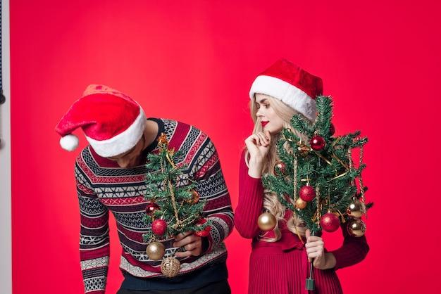 Casal jovem alegre em brinquedos de decoração de roupas de ano novo com fundo vermelho
