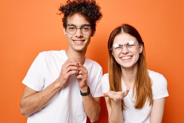 Casal jovem alegre em camiseta branca junto amizade fundo laranja