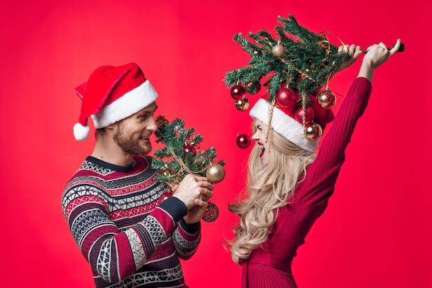 Casal jovem alegre em fundo vermelho de brinquedos de decoração de roupas de ano novo. foto de alta qualidade