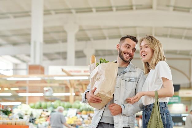 Casal jovem alegre em pé no mercado dos fazendeiros e conversando enquanto faz compras