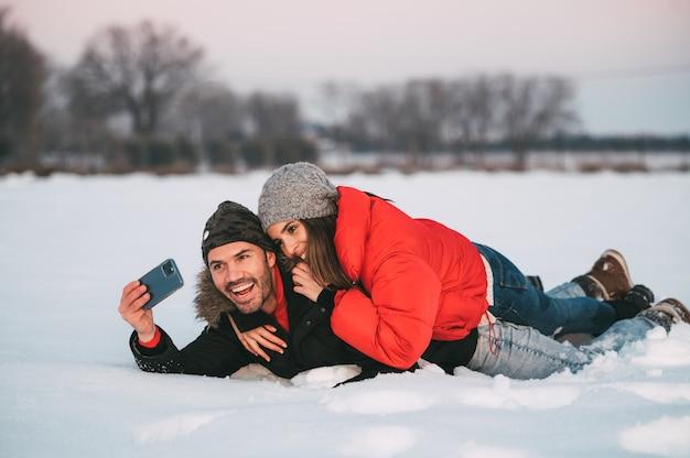 Casal jovem alegre em roupas quentes, deitado na neve e tirando uma selfie no smartphone enquanto se diverte no campo de inverno