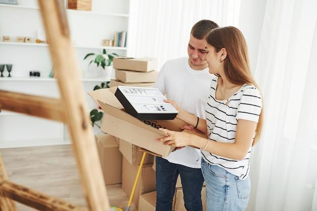 Casal jovem alegre em seu novo apartamento. concepção de movimento.